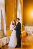 Coppie delle spose che ballano vicino alla finestra su fondo con l'interno di legno d'annata Fotografia Stock Libera da Diritti