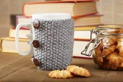 Coppie delle tazze di tè con le coperture ed i biscotti tricottati Fotografia Stock