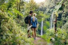 Coppie delle viandanti che osservano cascata Fotografia Stock