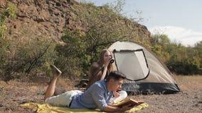 Coppie delle viandanti che riposano vicino alla tenda nel sole caldo archivi video