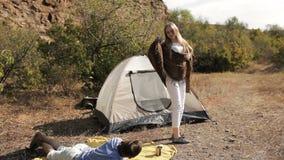 Coppie delle viandanti che riposano vicino alla tenda nel sole caldo video d archivio