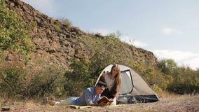 Coppie delle viandanti che riposano vicino alla tenda nel sole caldo stock footage