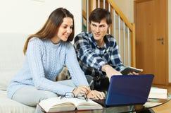 Coppie dello studente che fanno compito con il computer portatile Fotografie Stock