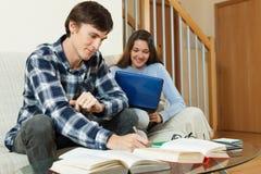 Coppie dello studente con i libri ed il computer portatile che preparano per gli esami Immagine Stock Libera da Diritti