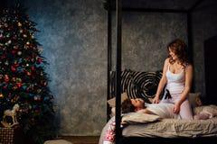 Coppie dentro in pigiami che riposano sul letto vicino all'albero di Natale Fotografie Stock