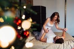 Coppie dentro in pigiami che riposano sul letto vicino all'albero di Natale Fotografie Stock Libere da Diritti