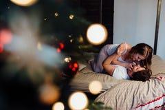 Coppie dentro in pigiami che riposano sul pavimento accanto al letto vicino all'albero di Natale Fotografia Stock Libera da Diritti
