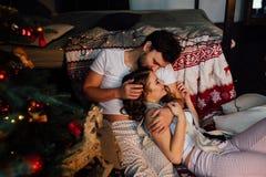 Coppie dentro in pigiami che riposano sul pavimento accanto al letto vicino all'albero di Natale Fotografia Stock