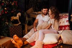 Coppie dentro in pigiami che riposano sul pavimento accanto al letto vicino all'albero di Natale Immagine Stock
