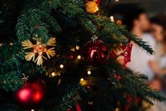 Coppie dentro in pigiami che riposano sul pavimento accanto al letto vicino all'albero di Natale Immagini Stock Libere da Diritti
