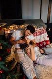 Coppie dentro in pigiami che riposano sul pavimento accanto al letto vicino all'albero di Natale Fotografie Stock Libere da Diritti