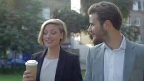 Coppie di affari che camminano attraverso il parco con caffè asportabile archivi video