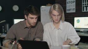 Coppie di affari che discutono i dati del documento nell'ufficio di notte video d archivio