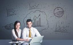 Coppie di affari con i diagrammi di affari Immagine Stock