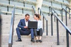 Coppie di affari con il computer portatile Immagini Stock