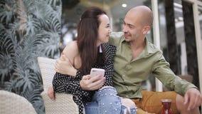 Coppie di amore che si siedono sullo strato ad un caffè all'aperto, ad un tè bevente, parlanti e prendenti un selfie sul vostro s archivi video
