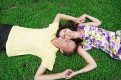 Coppie di amore che si trovano insieme sull'erba immagine stock libera da diritti