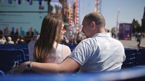 Coppie di amore sulle sedie blu in mezzo alla città che si siede alla conferenza che ascolta una conferenza tipo archivi video
