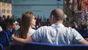 Coppie di amore sulle sedie blu in mezzo alla città che si siede alla conferenza che ascolta una conferenza tipo video d archivio
