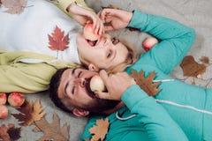 Coppie di autunno che mangiano mela e gli sguardi molto sensuale Le coppie divertenti stanno preparando per la vendita di autunno fotografia stock libera da diritti