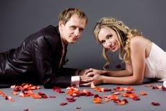 Coppie di cerimonia nuziale fra i petali di rosa immagini stock libere da diritti