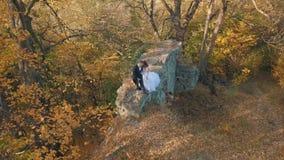 Coppie di cerimonia nuziale Sposo adorabile e sposa che si siedono sopra su un resti di una costruzione distrutta nella famiglia  archivi video