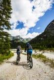 Coppie di ciclismo di montagna sulla polizia del lago Fotografia Stock