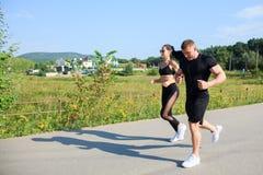 Coppie di forte allenamento dell'uomo e della donna di misura all'aperto Immagine Stock