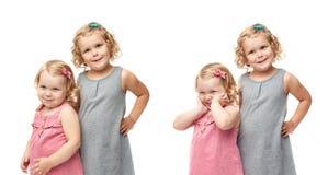 Coppie di giovani bambine che controllano fondo bianco isolato Immagini Stock Libere da Diritti