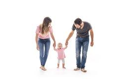Coppie di giovani genitori che aiutano il loro bambino a fare i primi punti sul pavimento nella loro casa Fotografie Stock
