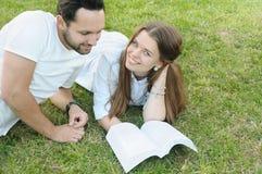Coppie di giovani studenti che studing sull'erba dalla città universitaria Fotografia Stock Libera da Diritti