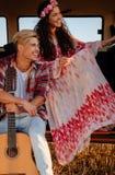 Coppie di hippy con la chitarra su un viaggio stradale Fotografia Stock Libera da Diritti