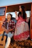 Coppie di hippy con la chitarra su un viaggio stradale Immagini Stock