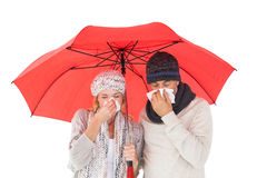 Coppie di modo di inverno che starnutisce sotto l'ombrello Immagini Stock