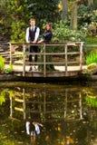 Coppie di modo vittoriano vicino al lago con le riflessioni in parco Immagini Stock