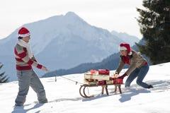 Coppie di natale che giocano con i regali nella neve Fotografia Stock