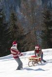 Coppie di natale che giocano con i regali nella neve Immagine Stock