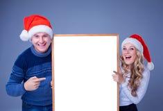 Coppie di Natale che tengono bordo bianco con vuoto Fotografia Stock