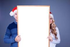 Coppie di Natale che tengono bordo bianco con vuoto Immagine Stock Libera da Diritti