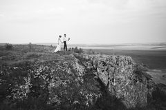 Coppie di nozze che guardano in collina della montagna sul tramonto Fotografia Stock