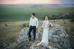 Coppie di nozze che guardano in collina della montagna sul tramonto Immagine Stock