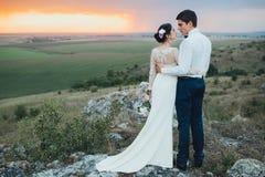Coppie di nozze che guardano in collina della montagna sul tramonto Fotografie Stock