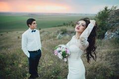 Coppie di nozze che guardano in collina della montagna sul tramonto Immagini Stock