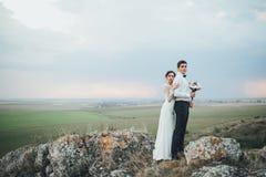 Coppie di nozze che guardano in collina della montagna sul tramonto Fotografie Stock Libere da Diritti