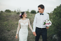 Coppie di nozze che guardano in collina della montagna sul tramonto Fotografia Stock Libera da Diritti