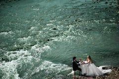 Coppie di nozze che si siedono alla tavola e che celebrano il loro marria Immagine Stock