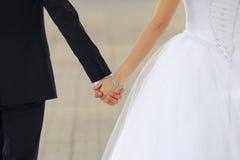 Coppie di nozze che si tengono per mano vicino su fotografie stock