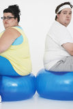 Coppie di peso eccessivo infelici che si siedono sulle palle di esercizio Immagini Stock