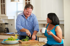 Coppie di peso eccessivo sulla dieta che prepara le verdure in cucina Fotografie Stock Libere da Diritti
