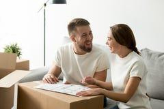 Coppie di risata felici che discutono piano architettonico della casa fotografia stock